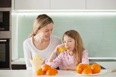 Η οικογένεια κάνει το χυμό από πορτοκάλι σε ένα juicer Στοκ φωτογραφία με δικαίωμα ελεύθερης χρήσης