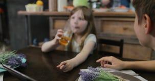 Η οικογένεια μαζί στην κουζίνα πριν από το γεύμα, γονείς πίνει το κρασί αγκαλιάζοντας ενώ τα παιδιά προσέχουν το βίντεο στην ψηφι απόθεμα βίντεο