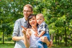Η οικογένεια με ένα παιδί στο πάρκο εξετάζει κάτι να ενδιαφέρει Στοκ φωτογραφία με δικαίωμα ελεύθερης χρήσης
