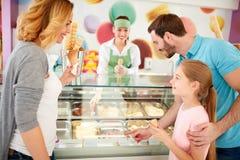 Η οικογένεια με την κόρη επιλέγει τις γεύσεις παγωτού στοκ εικόνα