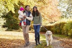 Η οικογένεια με την κόρη και το σκυλί απολαμβάνουν τον περίπατο επαρχίας φθινοπώρου στοκ φωτογραφία