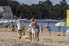Η οικογένεια με τρία παιδιά αφήνει την παραλία Στοκ Εικόνες