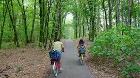 Η οικογένεια, πατέρας, μητέρα σε ένα φόρεμα, με ένα καλάθι των λουλουδιών, μαζί με τα μικρά παιδιά, οδηγά τα ποδήλατα, στο δάσος απόθεμα βίντεο