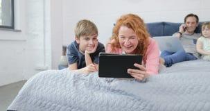 Η οικογένεια περνά το πρωί μαζί στα βίντεο ρολογιών μητέρων και γιων κρεβατοκάμαρων γελώντας πέρα από την ομιλία πατέρων στο τηλε απόθεμα βίντεο