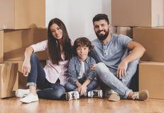 Η οικογένεια που κινείται προς τη νέα θέση και κάθεται στο πάτωμα Στοκ φωτογραφία με δικαίωμα ελεύθερης χρήσης