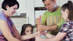 Η οικογένεια προετοιμάζει το εύγευστο γεύμα και τεντώνει την παχιά ζύμη απόθεμα βίντεο