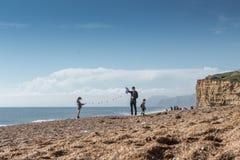 Η οικογένεια προετοιμάζεται να πετάξει έναν ικτίνο στην ηλιόλουστη παραλία Στοκ εικόνες με δικαίωμα ελεύθερης χρήσης
