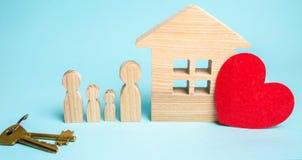 Η οικογένεια στέκεται κοντά στο σπίτι προσιτή κατοικία Ακίνητη περιουσία ομο στοκ φωτογραφίες με δικαίωμα ελεύθερης χρήσης