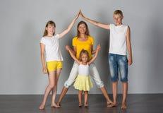Η οικογένεια στέκεται σε έναν γκρίζο στοκ εικόνα