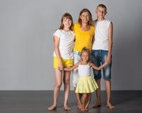Η οικογένεια στέκεται σε έναν γκρίζο στοκ φωτογραφία