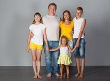 Η οικογένεια στέκεται σε έναν γκρίζο στοκ φωτογραφίες με δικαίωμα ελεύθερης χρήσης