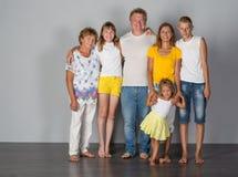 Η οικογένεια στέκεται σε έναν γκρίζο στοκ φωτογραφία με δικαίωμα ελεύθερης χρήσης