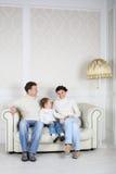 Η οικογένεια στα άσπρα πουλόβερ και τα τζιν κάθονται στον καναπέ στο σπίτι. Στοκ Φωτογραφίες