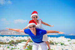 Η οικογένεια στα καπέλα Santa απολαμβάνει τις ελληνικές διακοπές με την όμορφη άποψη Στοκ εικόνα με δικαίωμα ελεύθερης χρήσης