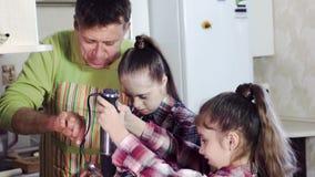 Η οικογένεια στην κουζίνα με έναν αναμίκτη κουζινών κτυπά τη ζύμη φιλμ μικρού μήκους