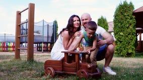 Η οικογένεια στις διακοπές στο πάρκο, ένας πατέρας που παίζει με το γιο του υπαίθρια το καλοκαίρι, Mom φιλά τον μπαμπά, γονείς απόθεμα βίντεο