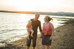 Η οικογένεια τριών ατόμων στέκεται στο ηλιοβασίλεμα και το σκηνικό θάλασσας στοκ εικόνες