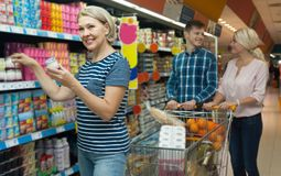 Η οικογένεια τριών ενηλίκων επιλέγει το γιαούρτι στο γαλακτοκομικό departme Στοκ Εικόνα
