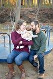 Η οικογένεια τριών στο πάρκο το φθινόπωρο σε εύθυμο πηγαίνει γύρω από Στοκ Εικόνες