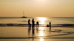 Η οικογένεια χαιρετίζει το ηλιοβασίλεμα στην παραλία Στοκ Φωτογραφία