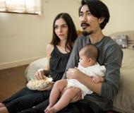 Η οικογένεια χαλαρώνει την ενότητα TV προσοχής στο σπίτι Στοκ φωτογραφία με δικαίωμα ελεύθερης χρήσης