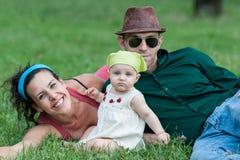 Η οικογένεια χαλαρώνει σε ένα λιβάδι Στοκ εικόνα με δικαίωμα ελεύθερης χρήσης