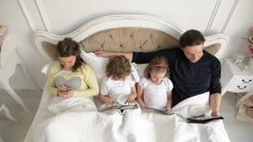 Η οικογένεια χρησιμοποιεί τις κινητές συσκευές μαζί στην κρεβατοκάμαρα κατά τη διάρκεια του Σαββατοκύριακου στο σπίτι Δύο παιδιά  φιλμ μικρού μήκους