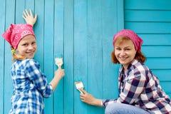 Η οικογένεια χρωματίζει έναν ξύλινο τοίχο του μπλε χρώματος Ιδέα της επισκευής Στοκ Εικόνα