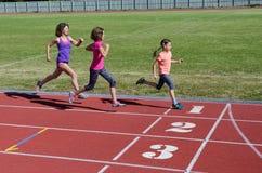 Η οικογενειακά ικανότητα, η μητέρα και τα παιδιά που τρέχουν στο στάδιο ακολουθούν, τον υγιή τρόπο ζωής κατάρτισης και αθλητισμού Στοκ Φωτογραφία