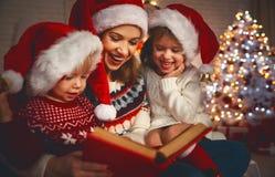 Η οικογενειακά μητέρα και τα παιδιά διαβάζουν ένα βιβλίο στα Χριστούγεννα firep πλησίον στοκ φωτογραφίες
