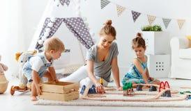 Η οικογενειακά μητέρα και τα παιδιά παίζουν έναν σιδηρόδρομο παιχνιδιών στο χώρο για παιχνίδη Στοκ Φωτογραφίες