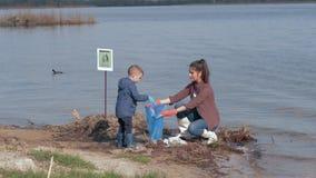 Η οικολογία φύσης προσοχής, αγόρι παιδιών βοηθά τη θηλυκή εθελοντική ακτή ποταμών ενεργών στελεχών καθαρή επάνω μολυσμένη από τα  απόθεμα βίντεο