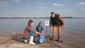 Η οικολογική προστασία φύσης, γονείς βοηθειών αγοριών παιδιών προσφέρεται εθελοντικά το καθαρό επάνω βρώμικο ανάχωμα ποταμών ενερ απόθεμα βίντεο