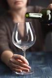 Η οινοπνευματώδης γυναίκα χύνει το κρασί σε ένα ποτήρι στην κουζίνα Στοκ εικόνα με δικαίωμα ελεύθερης χρήσης