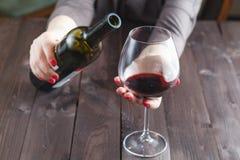 Η οινοπνευματώδης γυναίκα χύνει το κρασί σε ένα ποτήρι Στοκ Εικόνα