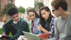 Η ομάδα έξυπνου και cheerfull οι σπουδαστές εργάζονται στο πρόγραμμα μελέτης κοντά στο κολλέγιο απόθεμα βίντεο