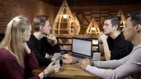 Η ομάδα ανθρώπων επικοινωνεί στον πίνακα στον καφέ στο εσωτερικό φιλμ μικρού μήκους