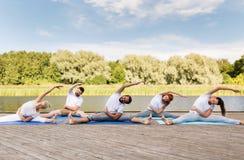Η ομάδα ανθρώπων που κάνει τη γιόγκα ασκεί υπαίθρια Στοκ Εικόνες