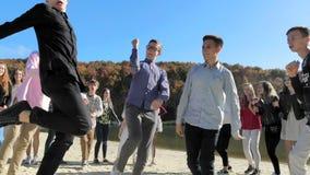 Η ομάδα ανθρώπων στην αμμώδη παραλία της λίμνης εκτελεί τους διάφορους χορούς Η έννοια των ευτυχών ανθρώπων ομάδας χορού απόθεμα βίντεο