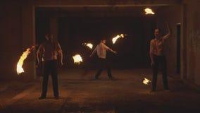 Η ομάδα αρσενικών καλλιτεχνών την ώρα της παράστασης την πυρκαγιά παρουσιάζει στο σκοτάδι σε σε αργή κίνηση φιλμ μικρού μήκους