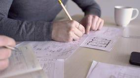 Η ομάδα αρχιτεκτόνων στο γραφείο εργάζεται με τα σχέδια στις σημειώσεις στο ημερολόγιο απόθεμα βίντεο