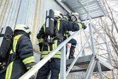 Η ομάδα διάσωσης μπαίνει σε το καίγοντας δωμάτιο στοκ εικόνα