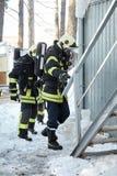 Η ομάδα διάσωσης μπαίνει σε το καίγοντας δωμάτιο στοκ εικόνες