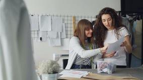 Η ομάδα δύο δημιουργικών σχεδιαστών επιλέγει το χρώμα των ράβοντας νημάτων για το ένδυμα που επισύρεται την προσοχή στο σκίτσο Οι απόθεμα βίντεο