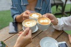 Η ομάδα ευθυμιών φίλων με τα latae κοιλαίνει στο φραγμό καφέδων με το τηλέφωνο στην επιτραπέζια συνεδρίαση υπαίθρια στον καφέ - ο στοκ εικόνες