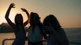 Η ομάδα ευτυχών νέων κοριτσιών χορεύει και πίνει στο κόμμα στο γιοτ στο φως ηλιοβασιλέματος κίνηση αργή φιλμ μικρού μήκους
