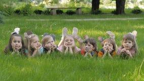 Η ομάδα ευτυχών παιδιών που βρίσκεται στην πράσινη χλόη υπαίθρια την άνοιξη σταθμεύει απόθεμα βίντεο