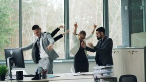 Η ομάδα εύθυμων συναδέλφων χορεύει στο γεγονός επιχείρησης εορτασμού γραφείων στο κόμμα, που ρίχνει τα έγγραφα, γελώντας και φιλμ μικρού μήκους