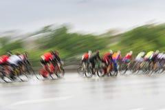 Η ομάδα ζωηρόχρωμων συναγωνιμένος ποδηλατών στο οδόστρωμα πόλεων, ημέρα, περίληψη, κίνηση θόλωσε το υπόβαθρο με το διάστημα αντιγ Στοκ Φωτογραφίες