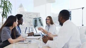 Η ομάδα καταρτισμένων γιατρών αναλύει την ακτίνα X των πνευμόνων ενός ασθενή Οι επαγγελματικοί γιατροί της πολυ εθνικής ομάδας εξ απόθεμα βίντεο
